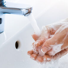 Woman uses soap to washing her hands under the sink faucet.